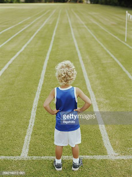 Boy (5-7) facing running track with hands on hips, rear view