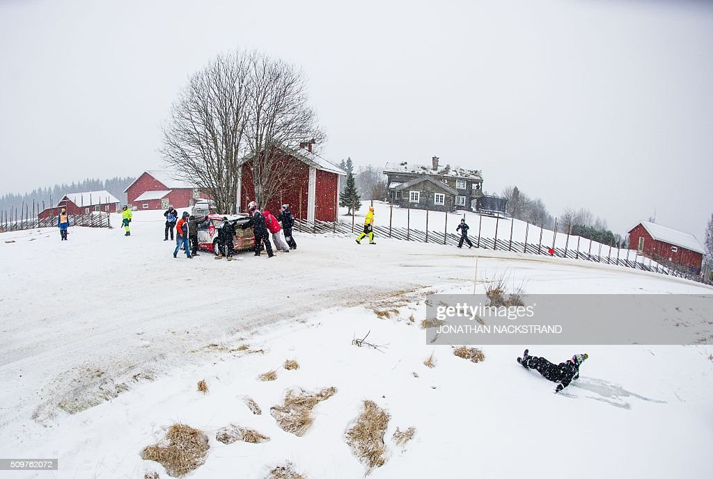 A boy falls on the ice as he tries to help Kris Meeke of Britain and his co-driver Paul Nagle of Ireland as they pull over their Citroen DS3 WRC due to a problem with the car wheels during the 8nd stage of the Rally Sweden, second round of the FIA World Rally Championship on February 12, 2016 in Rojden, near Svullrya, Norway. / AFP / JONATHAN NACKSTRAND