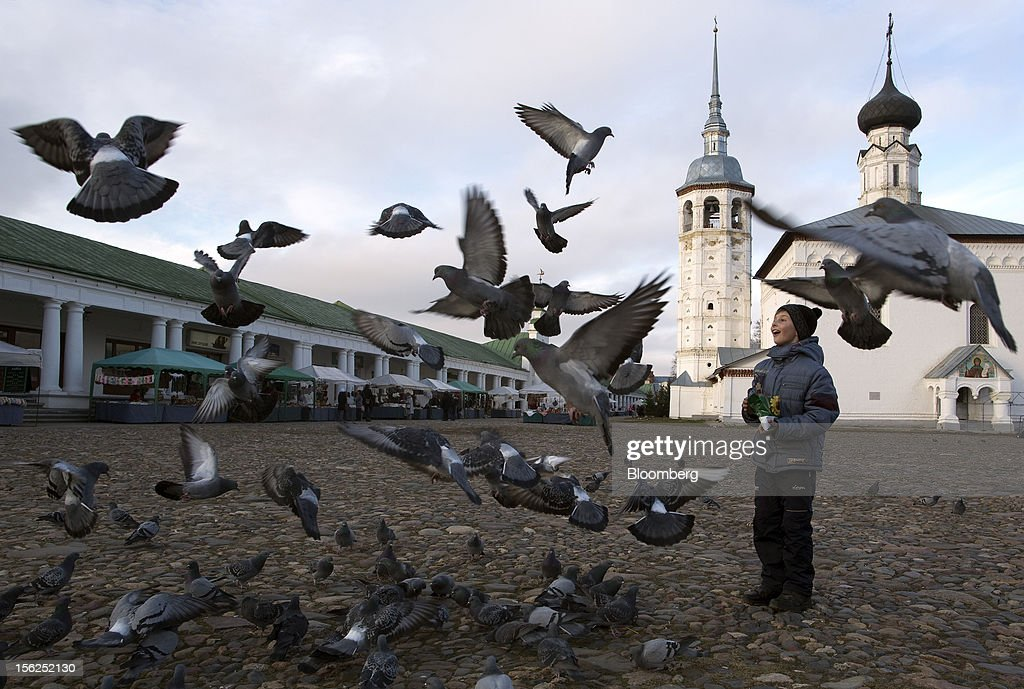 A boy feeds the pigeons in the central market square in Suzdal, Russia, on Sunday, Nov. 11, 2012. Russia has one of the world's lowest retirement ages, set in 1932 during the Stalin era. Photographer: Andrey Rudakov/Bloomberg via Getty Images