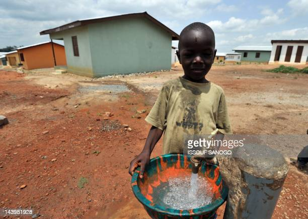 A boy fills a bucket with water from a tap on April 282012 in a 'new town' built by Koidu Holdings that provides access to clean drinking water...