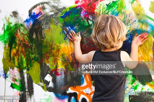 Boy finger painting on large canvas