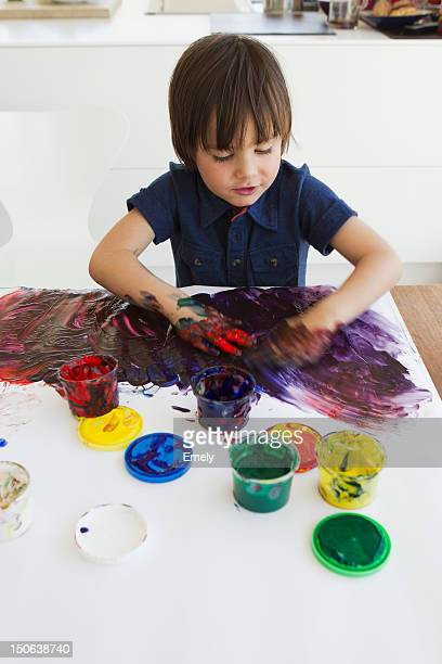 Boy finger painting on paper