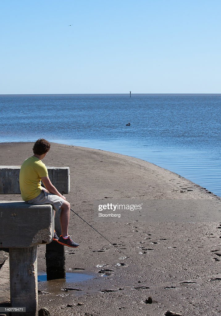 A boy fishes in the Gulf of Mexico in Waveland Mississippi US on Monday March 5 2012 BP Plc may face as much as $176 billion in civil pollution fines...