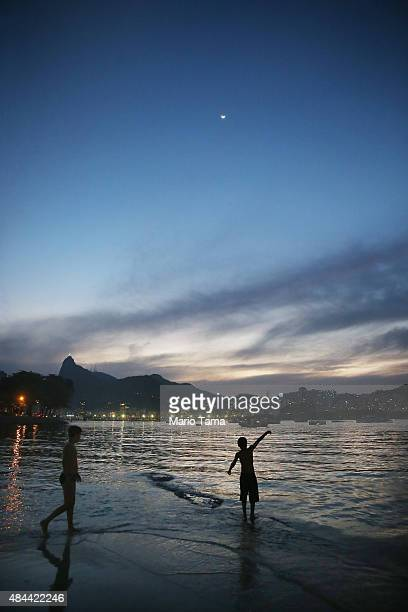 A boy fishes with the Christ the Redeemer statue in the background in the polluted Guanabara Bay the Rio 2016 Olympic Games sailing venue on August...