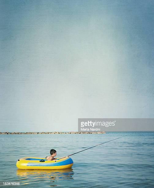 Boy fishing in boat