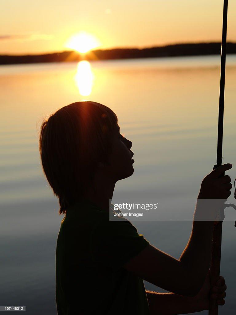 Boy fishing on sea at dusk : Stock Photo