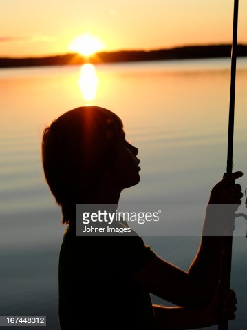Boy fishing on sea at dusk : Stock Photo