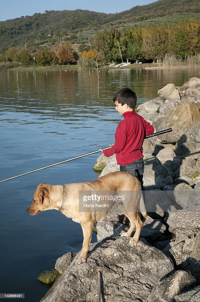 Boy fishing with dog on rocks : Stock Photo