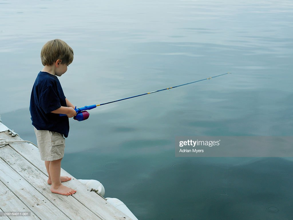 boy fishing with rod on jetty stock photo getty images