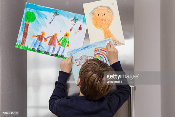 Boy fixed his drawings at fridge