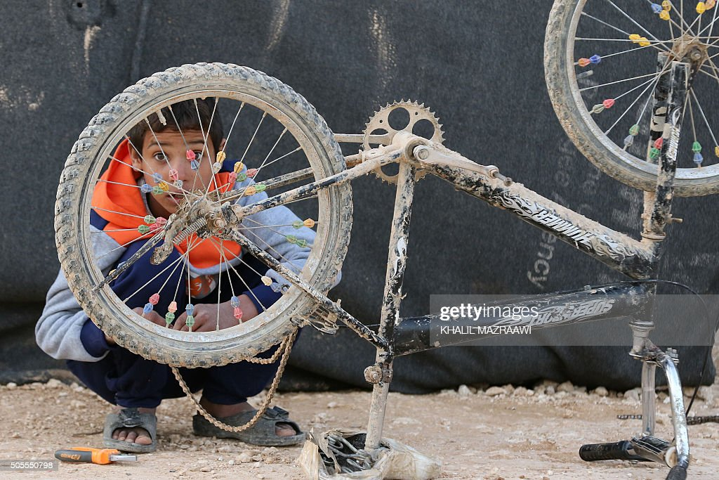 TOPSHOT A boy fixes his bike at Zaatari refugee camp close to the northern Jordanian city of Mafraq on January 18 2016 / AFP / KHALIL MAZRAAWI