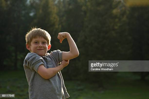 Boy flexes his muscles in wilderness on camp trip.