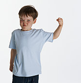 Boy (4-6) flexing bicep, pulling face, portrait