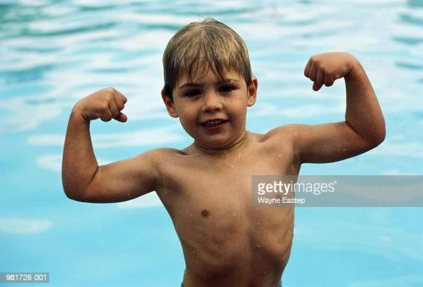 Boy (3-5) flexing muscles in foreground of pool, close-up