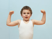 Boy (5-7) flexing muscles, portrait