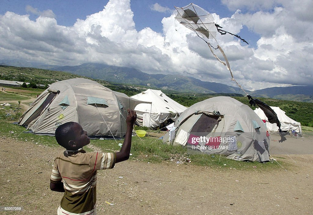 A boy flies a kite by tents in a makeshift camp on October 17, 2008 in the village of Cabaret, 35km north of Port-au-Prince, where some 700 people, mostly women and girls, have taken refuge after their homes were destroyed by hurricane Ike in September. AFP PHOTO/Thony BELIZAIRE