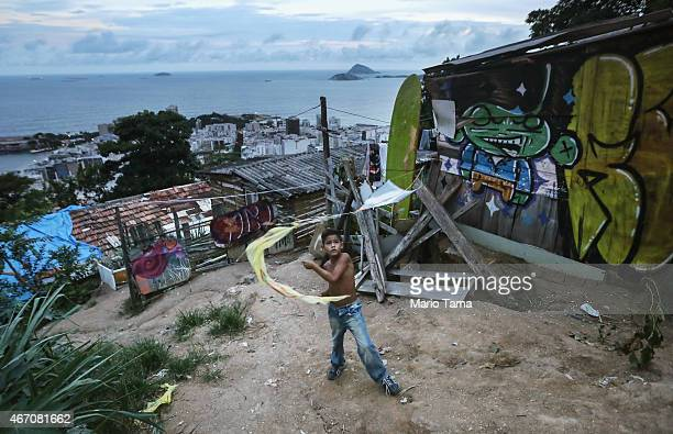 A boy flies a kite in a section where some houses are constructed with wood and mud in the 'pacified' PavaoPavaozinho 'favela' community on March 20...