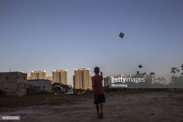 A boy flies a kite in an empty lot in front of the Ilha Pura property604 empty luxury apartments used by more than 18000 athletes during the Olympic...