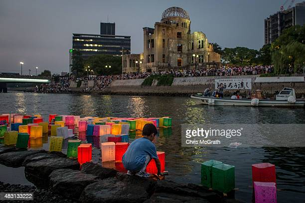 A boy floats a candle lit paper lantern on the river in front of the Atomic Bomb Dome during 70th anniversary activities commemorating the atomic...