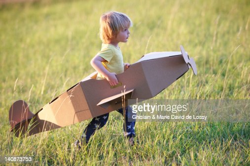 Boy flying airplane outdoors : Stock Photo