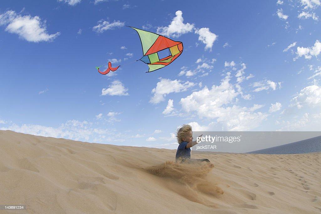 Boy flying kite on sand dune : Stock Photo