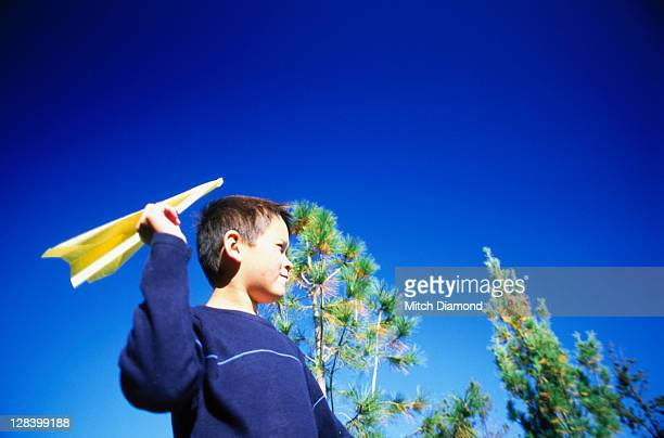 Boy flying paper plane
