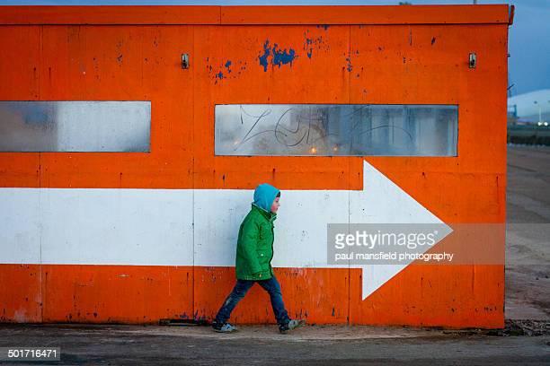 Boy following an arrow sign