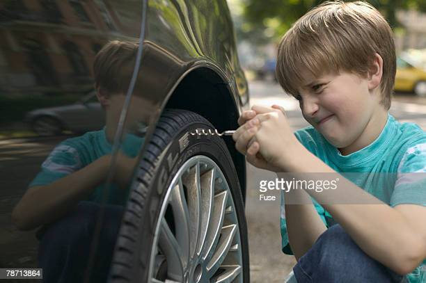 Boy Forcing Corkscrew into Car Tire