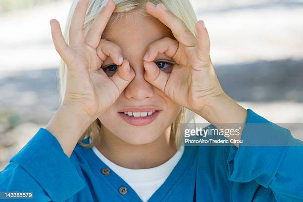 Boy forming circles with fingers around eyes