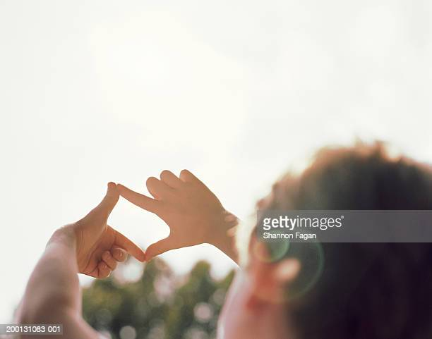 Boy forming frame against sky with fingers (focus on hands)