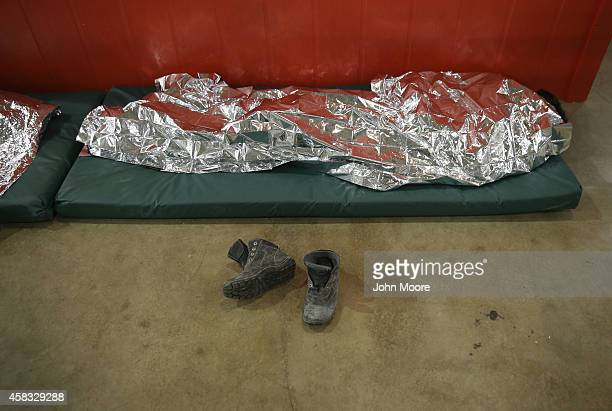 A boy from Central America rests under a thermal blanket at a detention facility run by the US Border Patrol on September 8 2014 in McAllen Texas The...