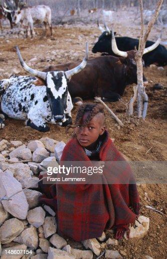 Boy from Himba tribe sitting near fire. : Stock Photo