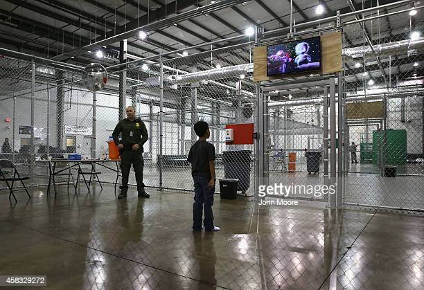 A boy from Honduras watches a movie at a detention facility run by the US Border Patrol on September 8 2014 in McAllen Texas The Border Patrol opened...