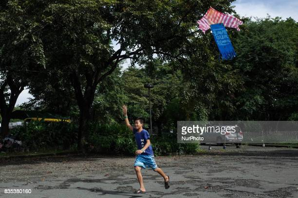 A boy from Mindanao residing at a makeshift school at the University of the Philippines International Center flies a kite in Quezon City on Saturday...
