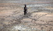 A boy from the remote Turkana tribe in Northern Kenya walks across a dryed up river at Kokuro on November 9 2009 near Lodwar Kenya Over 23 million...