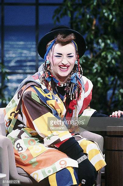 Boy George smiles as Joan Rivers pats her guest's hand during The Joan Rivers Show