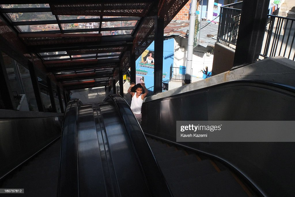 A boy gestures towards the camera while going down the escalators in '20 de Julio' neighborhood in the Comuna 13 slums on January 5, 2013 in Medellin, Colombia. The stairway is divided into six sections and has a length of 1,260 feet. An escalator goes up and a second goes down.Residents used to climb hundreds of steps to get home from the bottom of the hill, but the journey now takes just 6 minutes. Comuna 13 is the most notorious slums of Medellin with violence occurring everyday.
