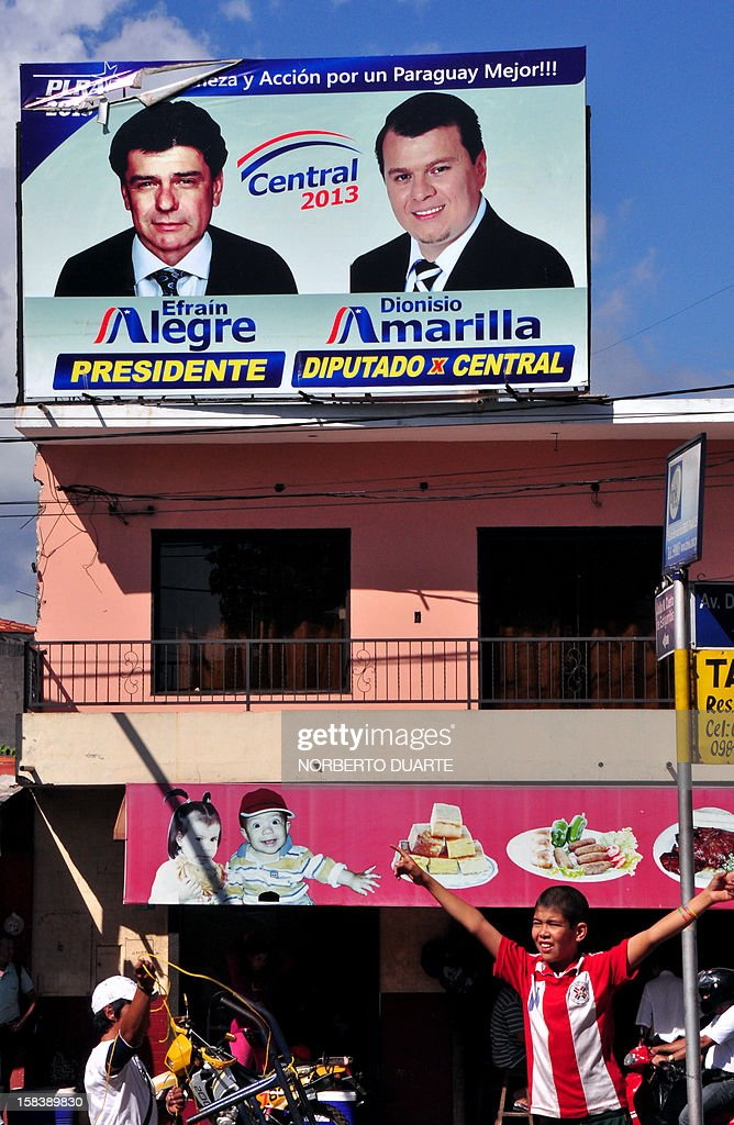 A boy gestures under a billboard with electoral propaganda of the presidential candidate of the Liberal Party, former Works Minister Efrain Alegre, in Asuncion on December 15, 2012. General elections will be held in Paraguay on April 21, 2013.