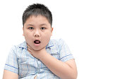 Obese boy gestures with something stuck in his throat isolated on white background, health care concept