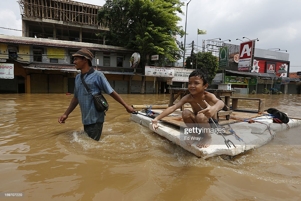 A boy gets a ride across a flooded road on a makeshift raft on January 19, 2013 in Jakarta, Indonesia. Floodwaters receded today after three days of heavy flooding which left thousands of people's homes underwater. According to Indonesian police the death toll has reached 15.