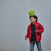 Boy gets hit by tennis ball on his head