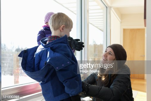 Boy getting dressed in winter clothing, mother helping