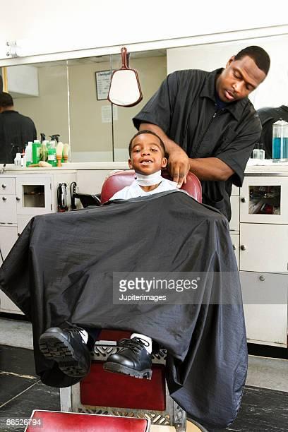 Boy getting haircut at barbershop