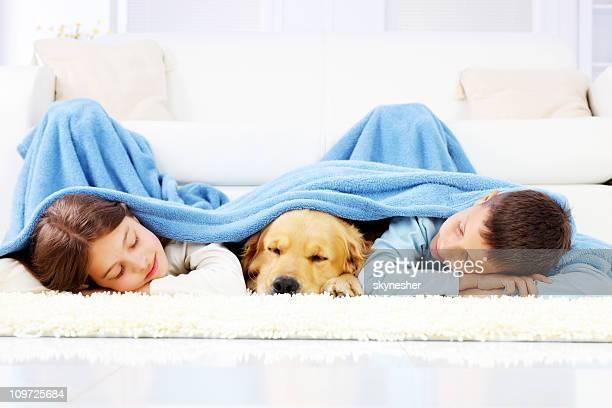 Jungen und Mädchen mit Hund Schlafen mit mit einer Decke.
