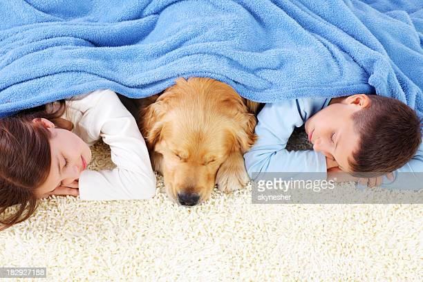 Ragazzo, ragazza e cane che dorme coperto con una coperta.
