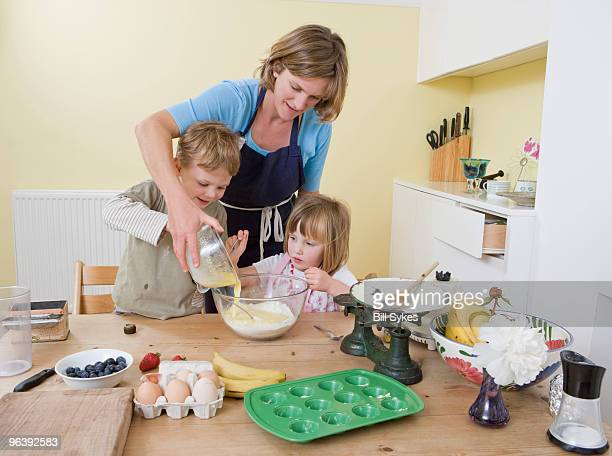 boy, girl and mum making fruit muffins