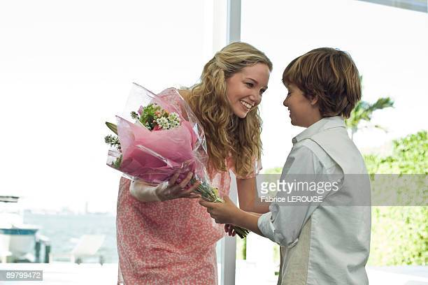 Boy giving a bouquet of flowers to her mother