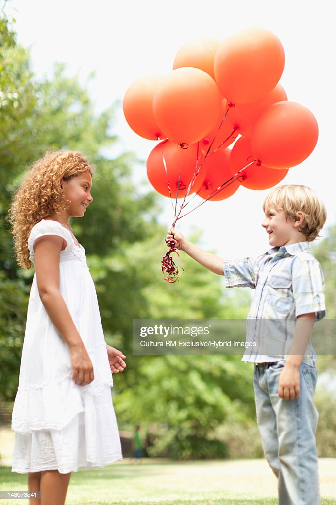 Boy giving girl bunch of balloons
