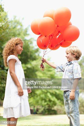 Boy giving girl bunch of balloons : Stock Photo