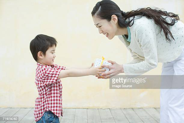 Boy giving his mother a gift